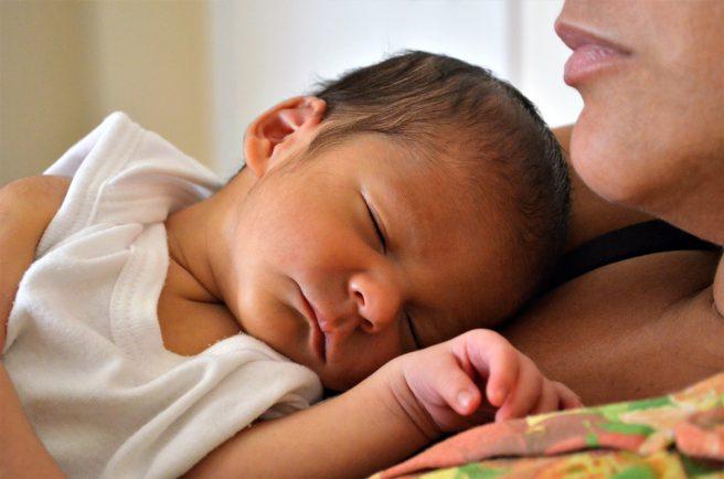 bebelus dormind pe pieptul mamei