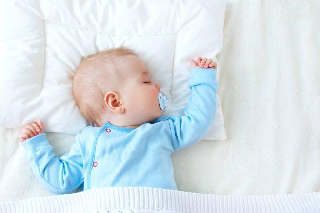 bebe cu suzeta in gura doarme intins pe perna