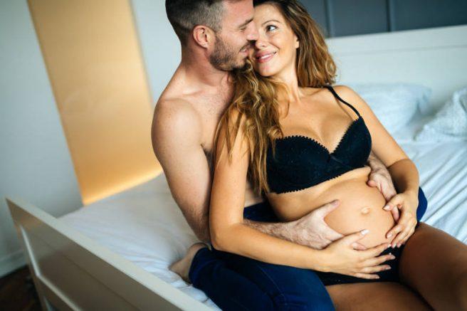 barbat imbratiseaza gravida pe pat