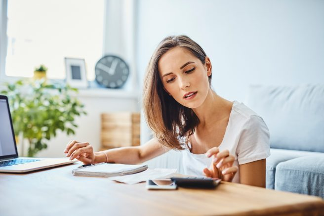 femeie-in-tricou-alb-sta-la-birou-cu-laptopul-in-fata-ei-si-face-niste-calcule-pe-un-calculator