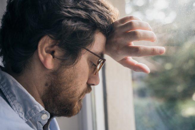 barbat-cu-ochelari-sta-sprijinit-de-o-fereastra-cu-mana-si-este-trist