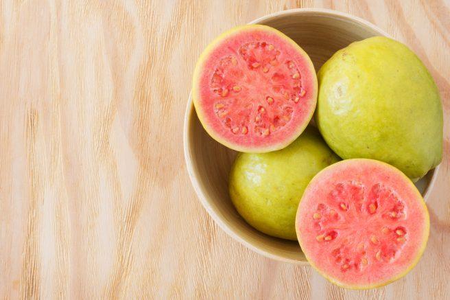 fructe-de-guava-intregi-intr-un-bol-si-un-alt-fruct-de-guava-taiat-ce-are-miezul-rosu-de-pe-lista-cu-fructe-recomandate-in-sarcina
