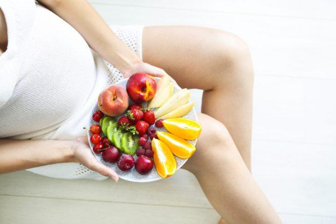 femeie-gravida-in-rochie-alba-tine-in-manini-o-farfurie-plina-cu-fructe