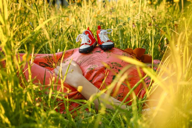 Femeie însărcinată în iarbă și o pereche de tenisi de bebelus