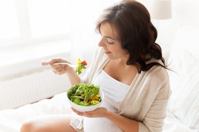 femeie-insarcinata-zambeste-si-tine-in-mana-un-bol-cu-salata-din-care-mananca-si-tine-regim-alimentar-pentru-colestaza-de-sarcina