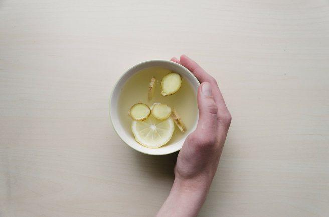 Femeie care ține în mână o cană de ceai cu ghimbir și lămâie