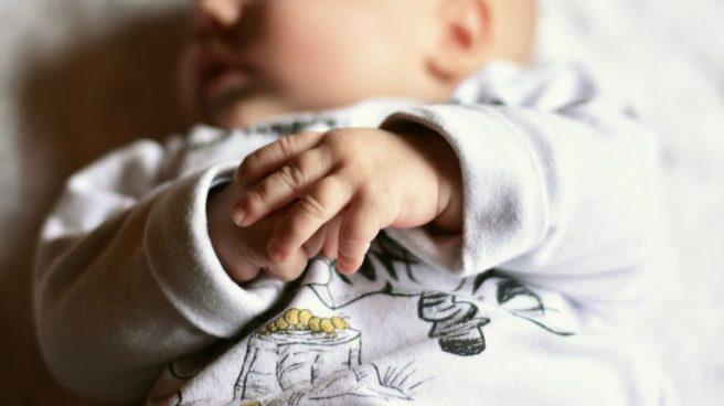 bebelus care doarme pe spate cu manutele impreunate pe burtica