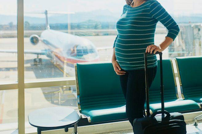 Femeie însărcinată în aeroport care se pregătește să zboare cu avionul.