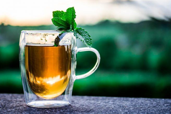 Pahar cu ceai de mentă și frunze de mentă.