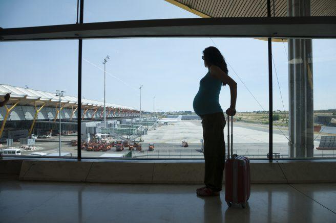 Femeie însărcinată în aeroport care se pregătește de zborul cu avionul