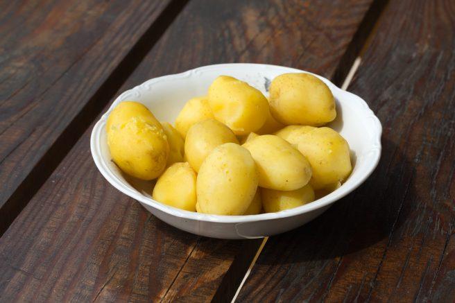 castron-alb--asezat-pe-o-masa-de-lemn-plin-cu-niste-cartofi-fierti-pentru-alimentatia-in-alaptare