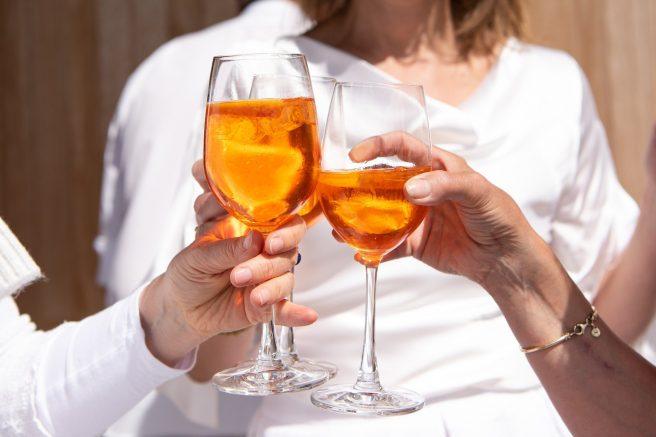 Trei femei care ciocnesc pahare de vin