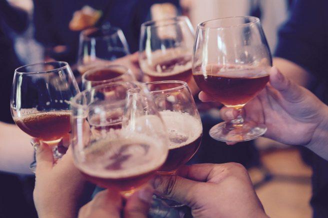 grup de persoane care tin in mana pahare cu alcool