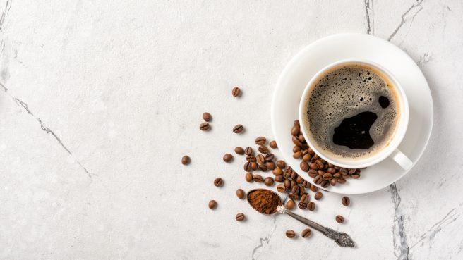ceasca-plina-cu-cafea-iar-langa-ea-sunt-boabe-de-cafea-si-o-lingurita-cu-niste-cafea-macinata