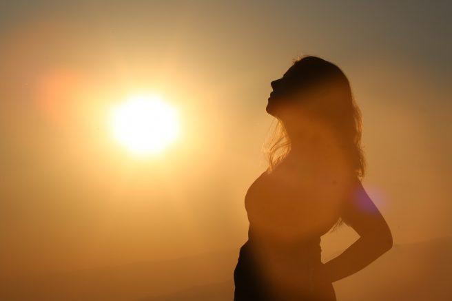 Femeie însărcinată bucurându-se de razele soarelui