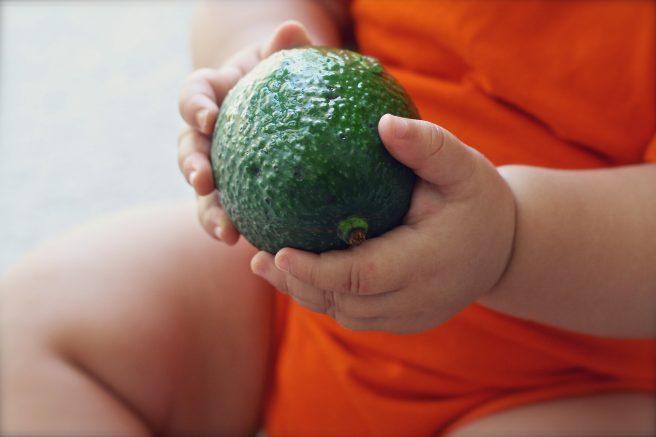 Bebeluș care ține în mână un avocado