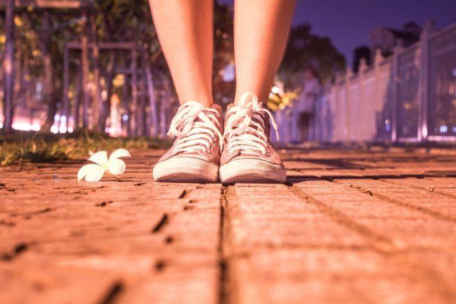 Picioare de femeie cu teneși pe stradă și o floare