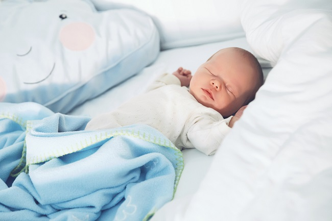 bebelus-care-doarme-pe-spate-cu-ajutorul-metodei-ferber-si-este-invelit-cu-o-patura-albastra