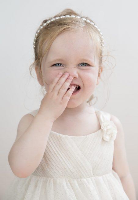 Fetiță cu rochie albă care ține mâna la nas
