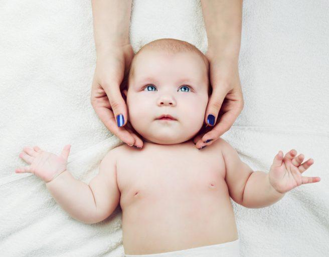 bebelus-care-sta-intins-pe-spate-si-este-cu-mainile-in-sus-si-i-se-face-masajul-bebelușului-pe-cap