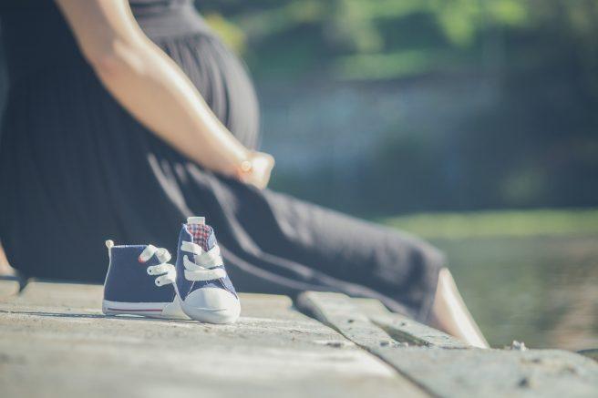 Femeie însărcintă și tenesi de bebelus