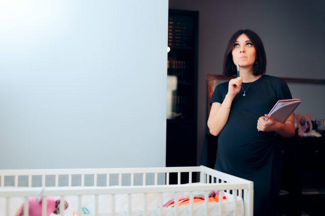 Femeie însărcinată care se gândește ce nume de fată să aleagă pentru copilul ei