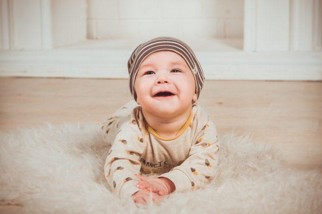 Băiețel care zâmbește pe covor