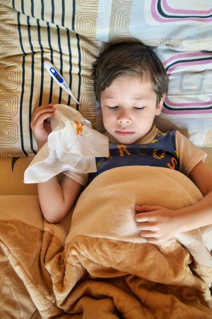 Copil răcit care stă în pat cu servețele și termometru