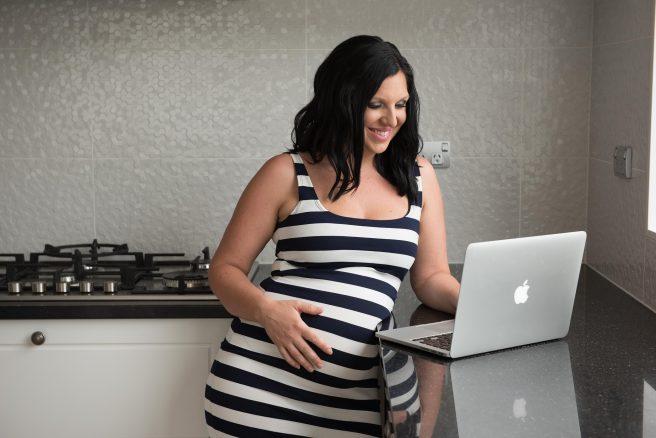 Femeie însărcinată care se uită pe laptop