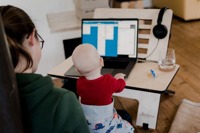 Mamă care lucrează la laptop și își ține copilul în brațe