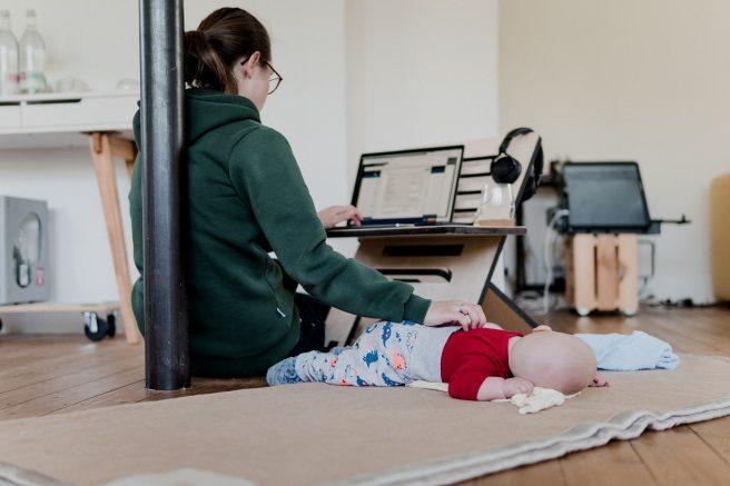 Mamă care lucrează și își mângâie copilul în același timp