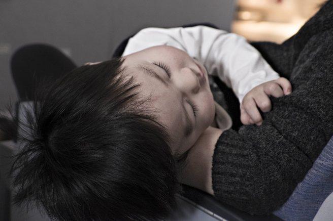 Bebelus care doarme in bratele mamei