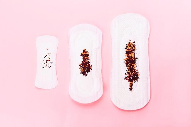 3-absorbante-pe-care-se-afla-scurgeri-colorate-maronii