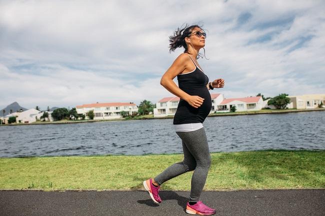 femeie-gravida-cu-ochelari-de-soare-care-alearga-pe-langa-un-lac-si-face-exercitii-in-sarcina
