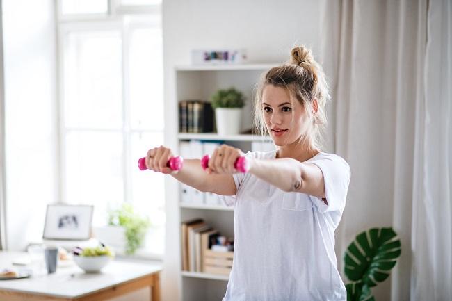 femeie-cu-tricou-alb-si-coc-are-greutati-roz-in-ambele-maini-si-face-exercitii-fizice-in-sarcina