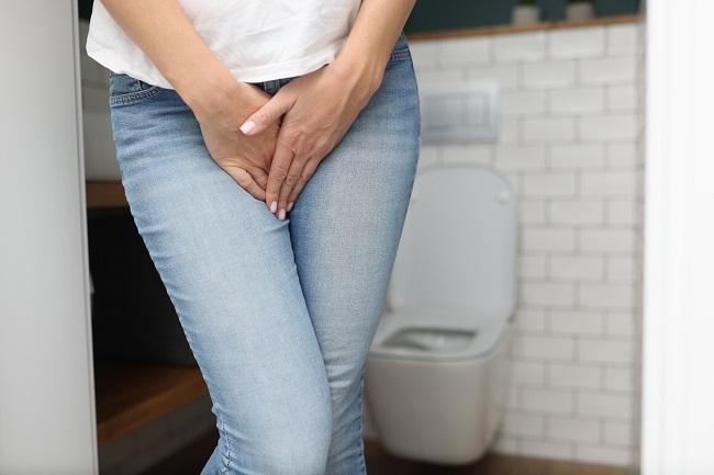 femeie-in-blugi-si-tricou-alb-care-este-langa-o-toaleta-si-are-secretii-vaginale-maronii