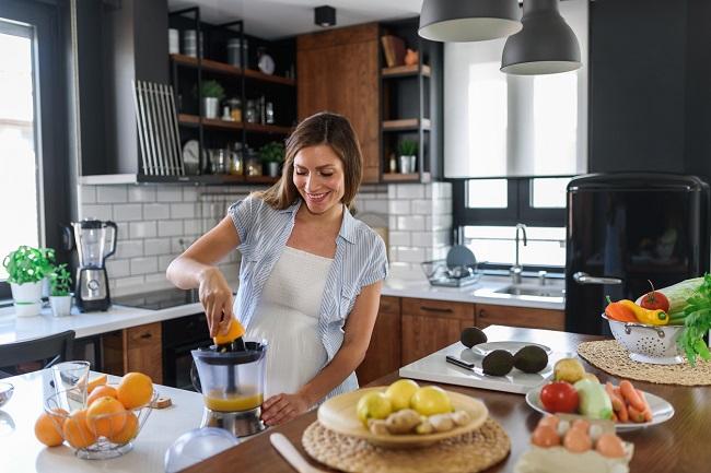 femeie-gravida-care-se-afla-in-bucatarie-si-prepara-suc-de-portocale-la-storcator