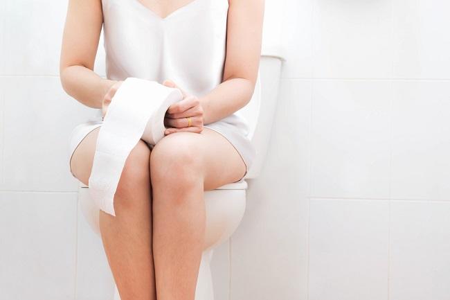 femeie-în-alb-care-stă-pe-toaletă-și-are-o-hârtie-igienică-în-mâini-și-suferă-de-constipație-după-cezariană
