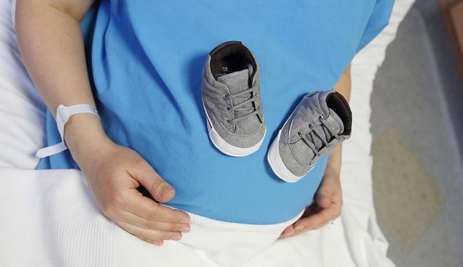 femeie-gravida-imbracata-cu-halat-de-spital-si-care-are-o-pereche-de-incaltari-pentru-bebe-pe-burta