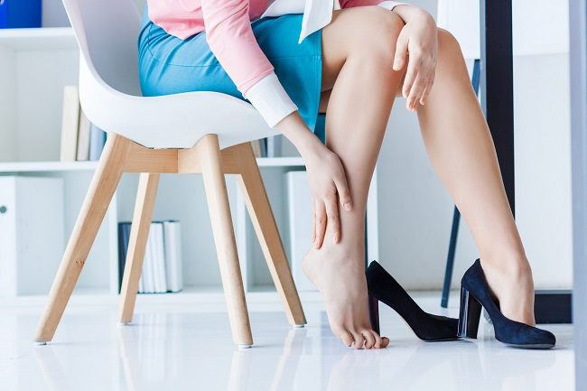 femeie-cu-fusta-albastra-care-sta-pe-scaun-alb-si-are-pantofi-cu-toc-negri-si-isi-atinge-gamba-cu-o-mana-dupa-nasterea-naturala-dupa-cezariana