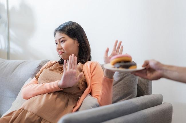 femeie-gravida-asiatica-care-refuza-mancarea-pentru-sucuri-de-fructe-si-hummus-in-sarcina