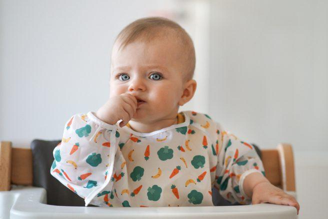 bebelus care sta in scaunul de masa