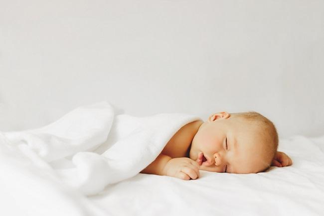 bebelus-care-doarme-invelit-cu-prosop-alb-si-care-trece-prin-regresia-somnului