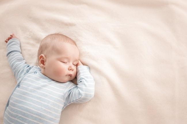 bebelus-care-este-imbracat-intr-o-salopeta-cu-dungi-albastre-si-albe-si-doarme-pe-spate