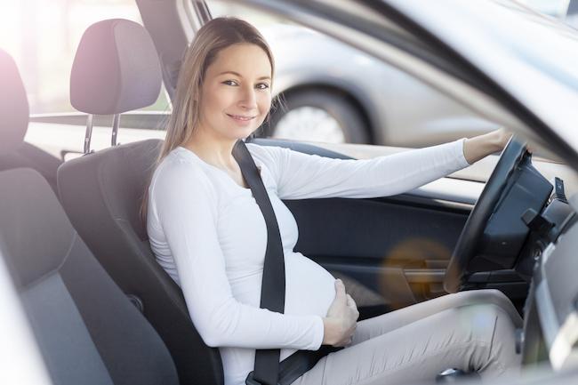 femeie-gravidă-care-stă-în mașină-cu-centura-de-siguranță-pusă-și-cu-mâna-pe-volan-fiind-exemplu-despre-cum-porți-centura-de-siguranță-când-ești-gravidă