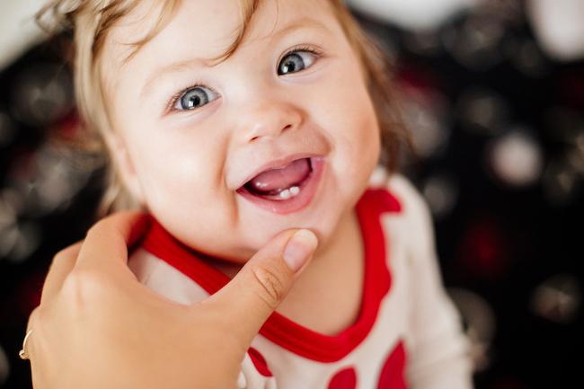 fetita-cu-bluza-rosie-cu-alb-care-sta-cu-gura-deschisa-si-are-doi-dinti-de-la-erupția-dentară