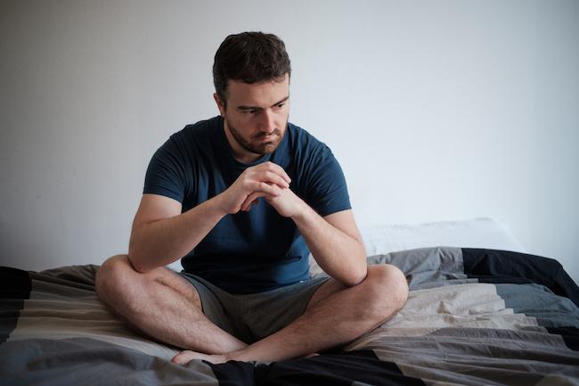 bărbat-trist-cu-probleme-de-infertilitate-la-bărbați-care-stă-în-șezut-în-pat