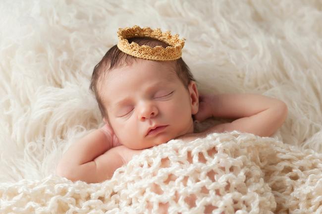 bebeluș-care-doarme-cu-mâinile-sub-cap-și-are-o-coroniță-pe-cap