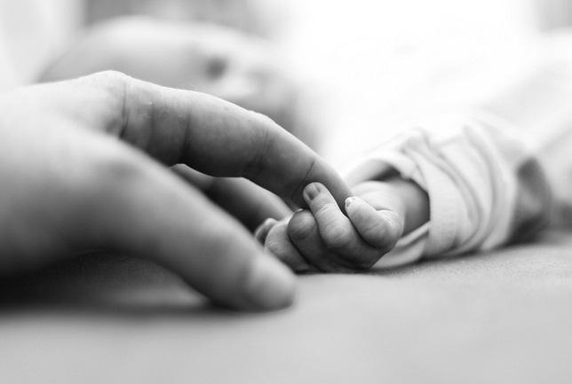poza-al-negru-cu-mana-unui-bebelus-cu-trisomia-18-si-a-unui-adult